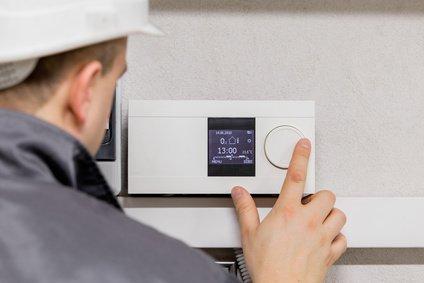 monteur bedient thermostat einer stromerzeugenden heizung