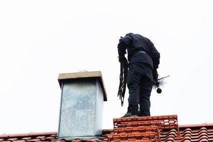 schornsteinfeger auf dem dach bei der arbeit