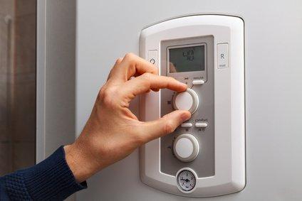 Mann reguliert die Temperatur der Heizung gemäß der Nennleistung