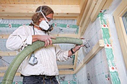 Handwerker führt Einblasdämmung aus