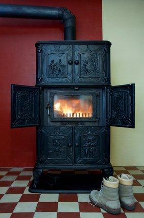 Winter-Wanderschuhe stehen vor Dauerbrandofen in einem alten Haus
