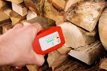 Hand mit Messgerät misst die Feuchtigkeit des Brennholz