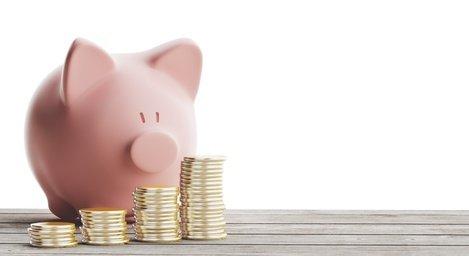 Sparschwein auf dem Tisch mit Geldstücken