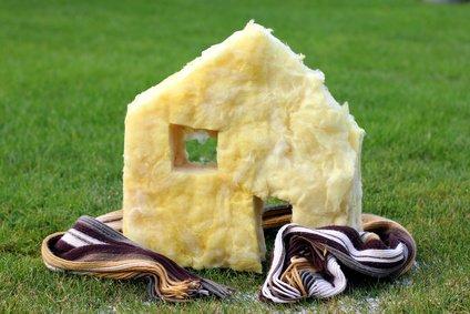 Wärmeschutzverordnung wird symbolisiert durch gedämmtes Haus mit Schal