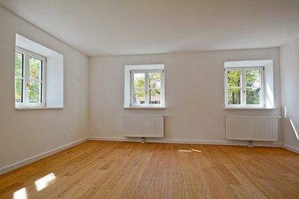 Wohnraum mit Holzboden und Heizkörpern an der Wand