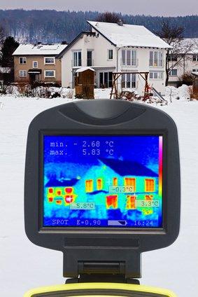 Energieberater nimmt Wärmebild eines Hauses auf