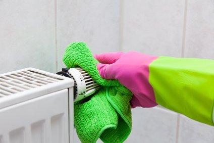 Heizung reinigen Hand mit Lappen
